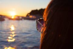 Фото женщины смотря заход солнца на пляже Стоковая Фотография RF