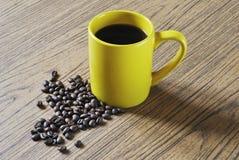 Фото желтых чашки кофе и кофейных зерен на деревянной предпосылке текстуры Стоковые Фото