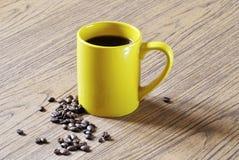 Фото желтых чашки кофе и кофейных зерен на деревянной предпосылке текстуры Стоковые Изображения
