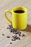 Фото желтых чашки кофе и кофейных зерен на деревянной предпосылке текстуры Стоковое Изображение