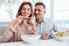 Фото жизнерадостных пожененных пар имея обедающий, и photog женщины Стоковые Изображения