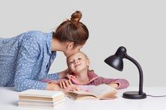Фото забот молодой женщины ее ребенка, целует дочь в лбе, хвалит ее для того чтобы изучить хорошо, объясняет материальные, прочит стоковые изображения