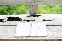 Фото запаса: Раскройте тетрадь и ручку белизны на старом деревянном backgrou стоковые фото