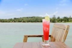 Фото запаса - стекла коктеиля на деревянном столе, стороне пляжа Стоковые Фотографии RF