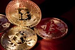 Фото золотое Bitcoins на красной предпосылке торгуя концепция секретной валюты Стоковые Изображения RF