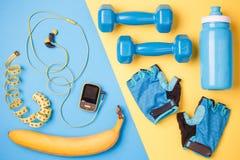 Фото игрока, гантелей, бутылки воды, ленты сантиметра, перчаток, банана на голубой и желтой предпосылке Стоковое Изображение RF