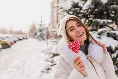 Фото конца-вверх заколдовывать длинн-с волосами девушку идя на снежную улицу с леденцом на палочке Милая смеясь женщина в связанн стоковое изображение rf