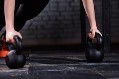 Фото конца-вверх молодых рук ` s женщины спортсмена пока делающ нажмите поднимает на kettlebells против кирпичной стены в спортза Стоковые Изображения