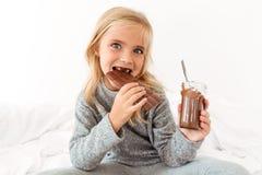 Фото конца-вверх смешной девушки есть шоколадный батончик смотря кулачок Стоковое Изображение