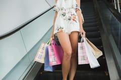 Фото конца-вверх сногсшибательных ног на покупках, стоящ с красочными хозяйственными сумками, ходя по магазинам концепция Стоковое Фото