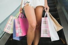 Фото конца-вверх сногсшибательных ног на покупках, стоящ с красочными хозяйственными сумками, ходя по магазинам концепция Стоковая Фотография RF