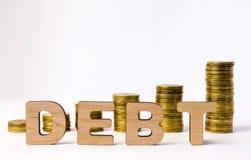 Фото концепции задолженности Слово задолженности от объемных писем 3D в переднем плане к предпосылке столбцов или стогам монеток  Стоковая Фотография RF