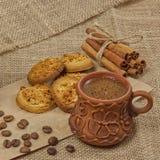Фото кофейной чашки, кофейных зерен, циннамона, печений и свечи стоковое изображение