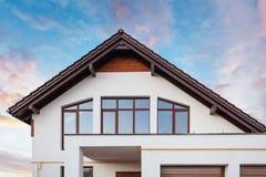Фото красивого комфорта и нового дома с окнами коричневой крыши большими и белой стеной против спокойного голубого неба стоковое фото