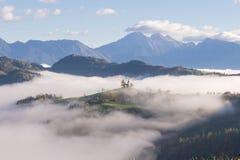 Фото красивого ландшафта восхода солнца церков St. Thomas в Словении на вершине холма в тумане утра стоковое фото rf