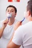 Фото красивого молодого человека брея и смотря себя в th Стоковое Фото