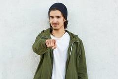 Фото красивого парня указывает с указательным пальцем на камеру, выражает его одетый выбор, в зеленом анораке и черном headgear,  стоковая фотография rf