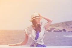 Фото красивой молодой женщины на шлюпке перед морем и I Стоковые Изображения