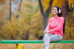 Фото красивой молодой женщины сидя на стенде в наушниках Стоковая Фотография RF