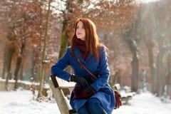 Фото красивой молодой женщины сидя на стенде в парке Стоковое фото RF