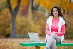 Фото красивой молодой женщины сидя на стенде с компьтер-книжкой Стоковые Фото