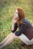 Фото красивой молодой женщины сидя на траве в wonde Стоковое фото RF