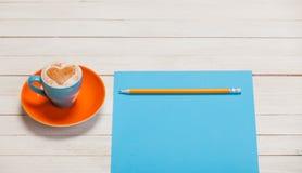 Фото красивых голубых чашки кофе и листа бумаги с pe Стоковое Фото