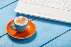Фото красивых голубых чашки кофе и компьтер-книжки на wonderfu Стоковая Фотография
