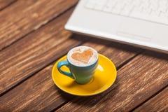 Фото красивых голубых чашки кофе и компьтер-книжки на wonderfu Стоковое Изображение