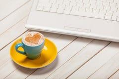 Фото красивых голубых чашки кофе и компьтер-книжки на wonderfu Стоковые Фотографии RF