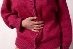 Фото крупного плана женщина имеет боль в ее животе, и держит ее руки Концепция женской медицины Пищеварительные проблемы, gynecol стоковое фото