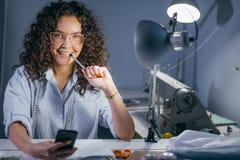Фото крупного плана молодой женщины имея карандаш в рте с сотовым телефоном на работе Стоковые Изображения