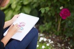Фото крупного плана красить рук женщины подняло с акварелью Стоковые Изображения