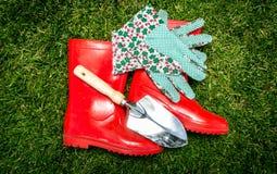 Фото крупного плана садовых инструментов и красных gumboots лежа на траве Стоковое Изображение
