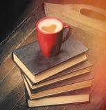 Фото кучи книг и чашки кофе на чудесном коричневом цвете Стоковое фото RF