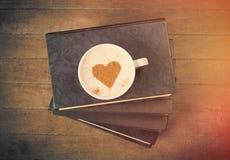 Фото кучи книг и чашки кофе на чудесном коричневом цвете Стоковая Фотография