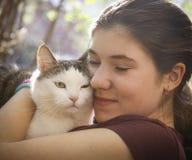 Фото лета солнечное девушки подростка обнимая кота Стоковые Фото