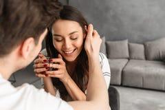 Фото любящих пар сидя на таблице в плоском и выпивая чае Стоковая Фотография RF