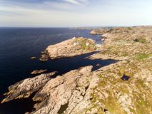 Фото маяка в лете, южной Норвегии Lindesnes Воздушная съемка Скалистое морское побережье и голубое небо Стоковая Фотография