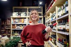 Фото молодого брюнета с бутылкой вина в руке стоковая фотография