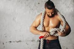 Фото молодого человека в sportswear вяжет узел Прочность и мотивировка стоковые изображения