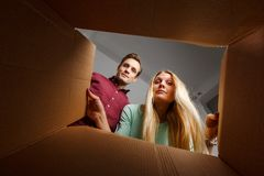 Фото молодой женщины и человека смотря внутри картонной коробки стоковая фотография rf