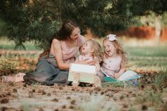 Фото молодой матери с 2 милым детей чтения книги временем outdoors весной, счастливой семьи, концепции Дня матери стоковое изображение rf