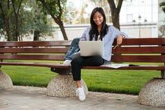 Фото молодой счастливой азиатской студентки ослабляя с компьтер-книжкой, Стоковые Изображения