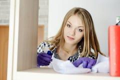 Фото молодой женщины пылясь книжные полки и смотря камеру Стоковое фото RF