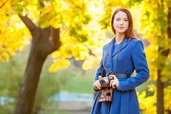 Фото молодой женщины с ретро камерой на чудесной осени t Стоковые Фотографии RF