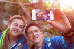 Фото молодой семьи внешнее принимая с мобильным телефоном Стоковое фото RF