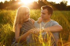 Фото молодых пар сидя на траве смотря один другого при влюбленность держа ` s одина другого вручает ослаблять outdoors Romanti Стоковые Изображения RF