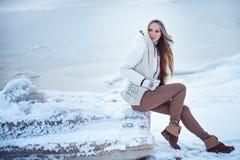 Фото моды внешнее шикарной женщины с длинными белокурыми волосами носит роскошное белое пальто, представляя на ледяном поле Стоковое Изображение