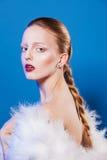 Фото моды красивой дамы в белых пер одевает На голубой предпосылке стоковое изображение rf